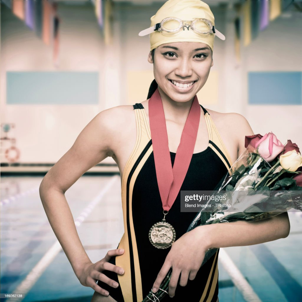 Mixed race swimmer with medal and flowers : Stock Photo