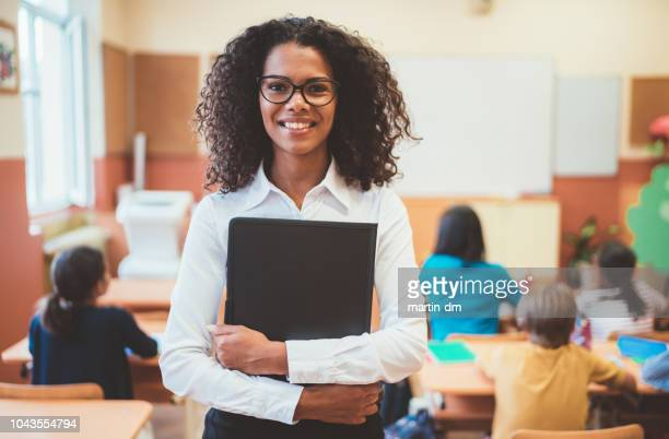 mixed race teacher in the classroom - teacher stock pictures, royalty-free photos & images