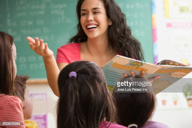 mixed race teacher reading to students - spelling stock pictures, royalty-free photos & images