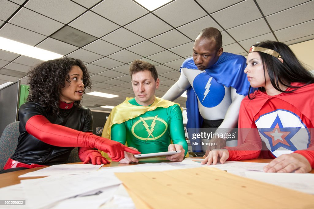 A mixed race team of office super heros in their office. : Stock Photo