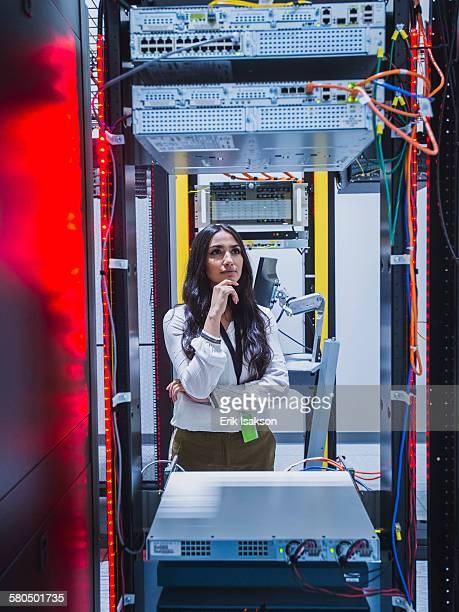 Mixed race technician examining computer in server room