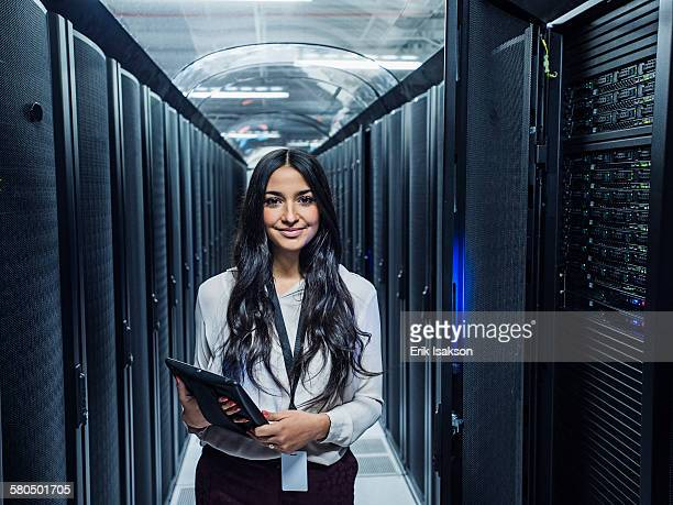 Mixed race technician holding digital tablet in server room