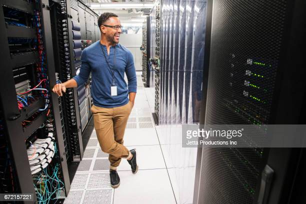 Mixed Race technician laughing in computer server room