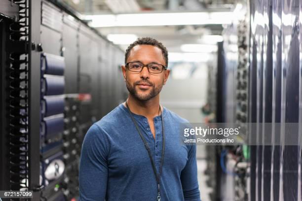 mixed race technician posing in computer server room - técnico - fotografias e filmes do acervo