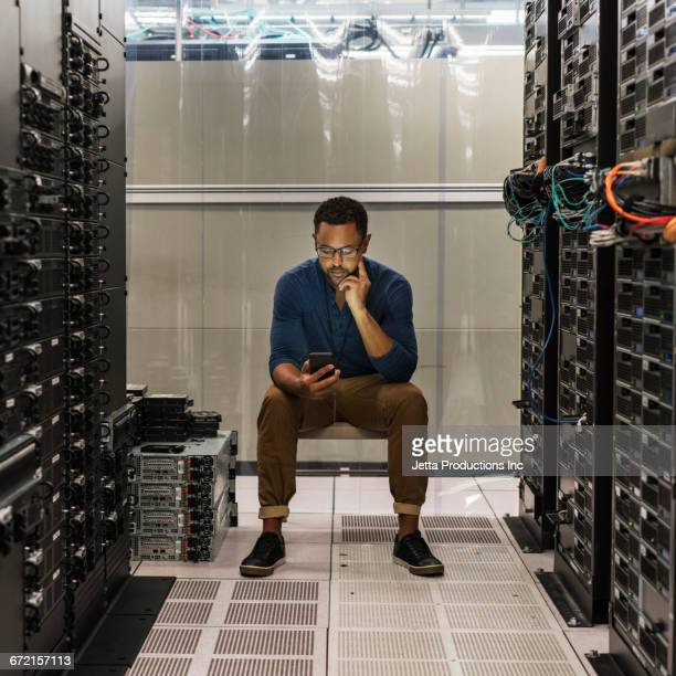 Mixed Race technician texting on cell phone in computer server room