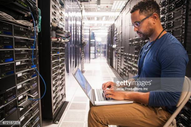 Mixed Race technicians using laptop in computer server room