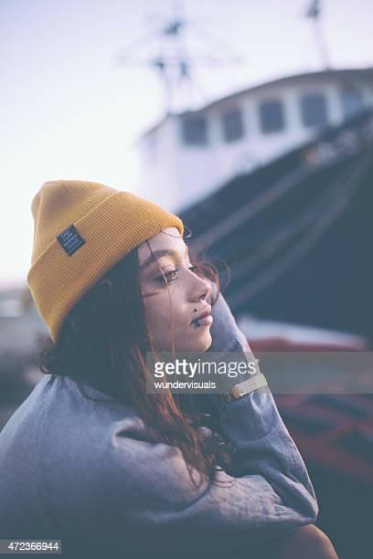 Mixed race teen grunge girl with facial piercings outdoors