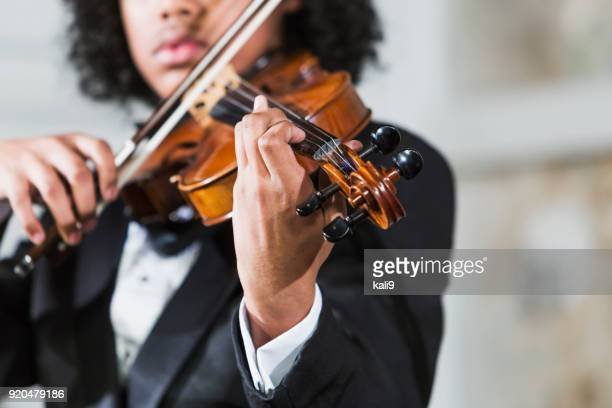 mixed race teenage boy playing the violin - violin family stock photos and pictures
