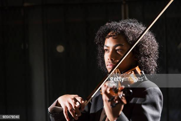 Mixed race teenage boy playing the violin