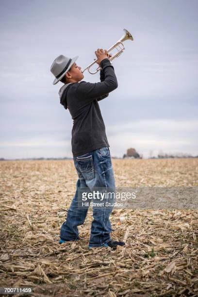 Mixed Race teenage boy playing trumpet in field