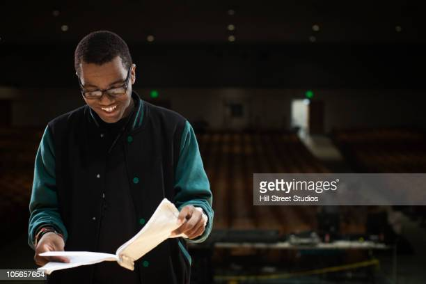 mixed race teenage boy rehearsing on stage - rehearsal stock pictures, royalty-free photos & images