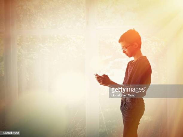Mixed race teenage boy using cell phone
