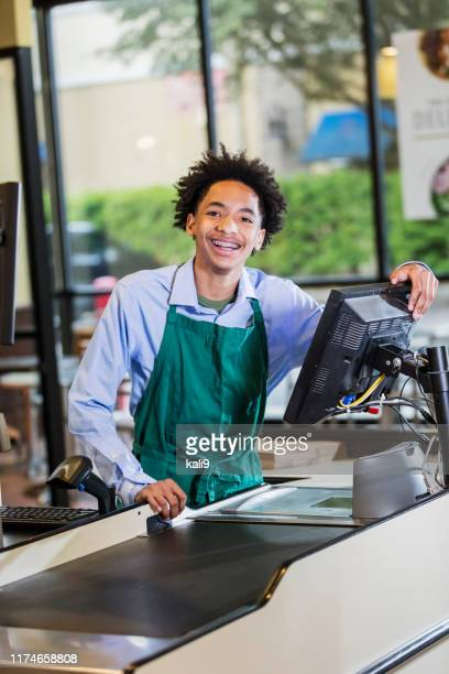 mixed race teenage boy working as supermarket cashier - teenagers only stock pictures, royalty-free photos & images