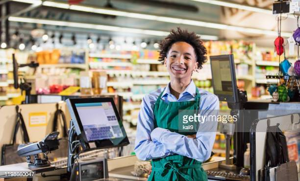 mixed race teenage boy working as supermarket cashier - teenager stock pictures, royalty-free photos & images