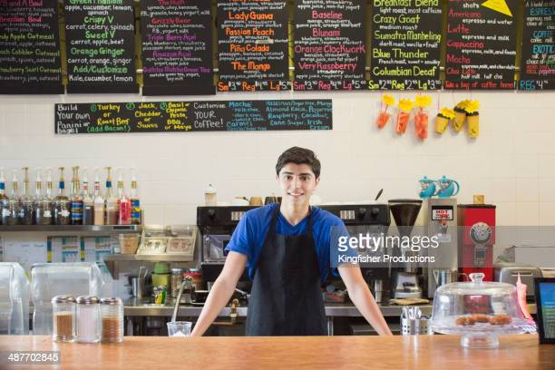 Mixed race teenage boy working in cafe