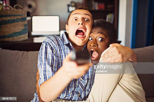 mixed race teenage couple watching a movie at home - scary movie stock photos and pictures