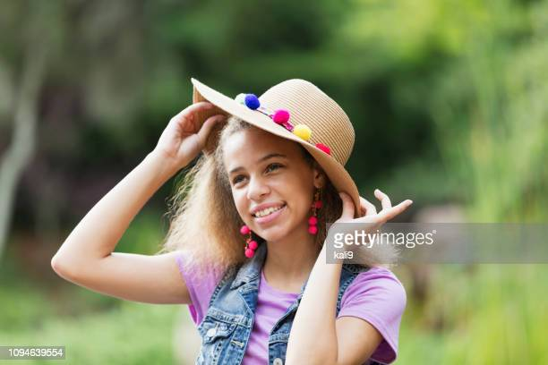 mixed race teenage girl at the park with wide brim hat - wide brim stock pictures, royalty-free photos & images