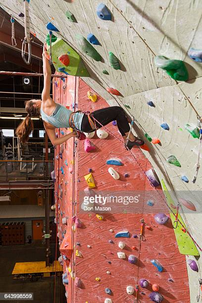 Mixed race teenage girl climbing rock wall