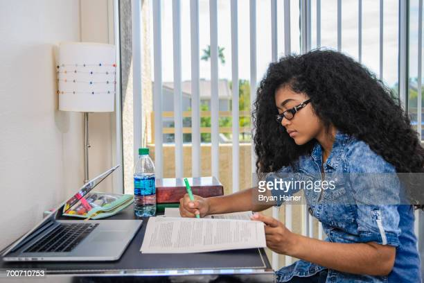 Mixed Race teenage girl doing homework at desk