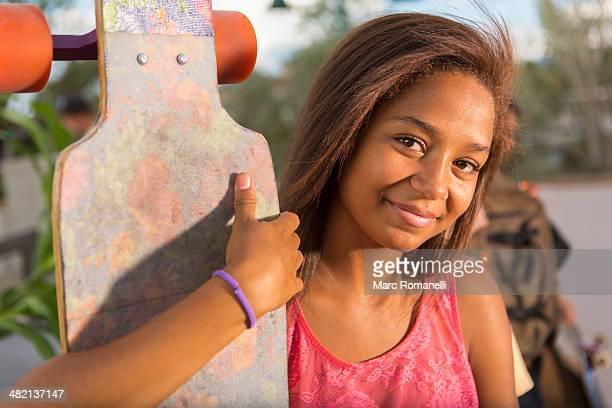 Mixed race teenage girl holding skateboard outdoors