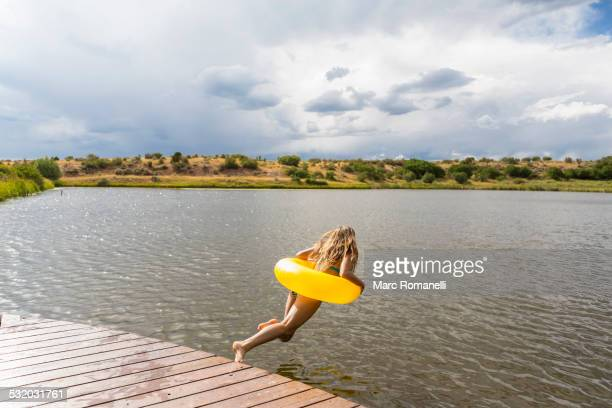 Mixed race teenage girl in inflatable ring jumping into still lake