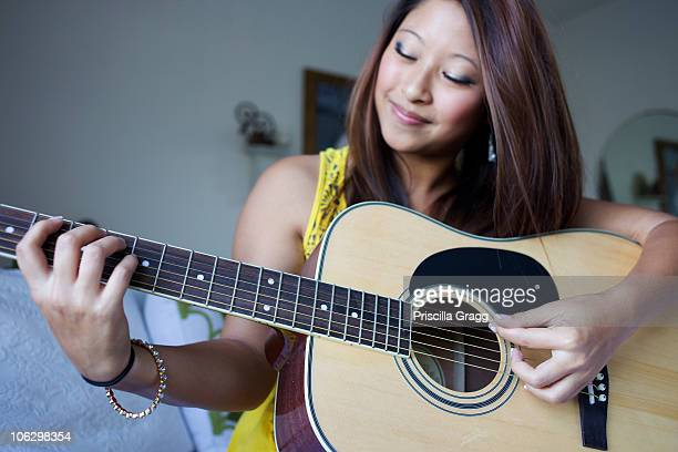 mixed race teenage girl playing guitar - plucking an instrument stock pictures, royalty-free photos & images
