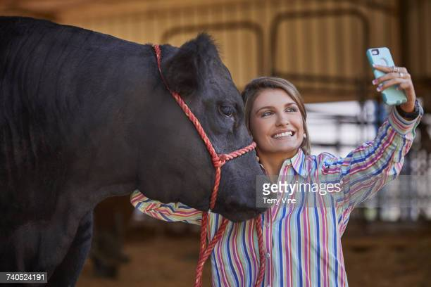 Mixed Race teenage girl posing for cell phone selfie with cow