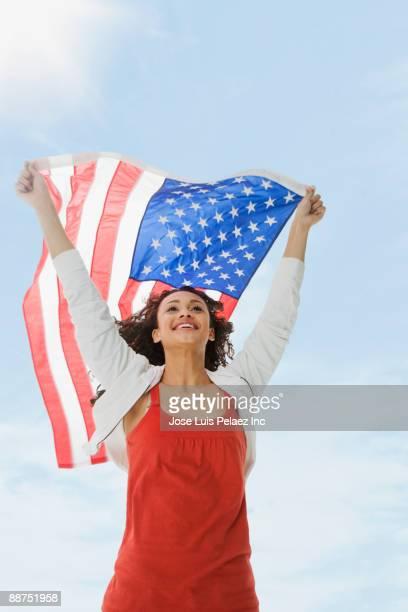 Mixed race teenage girl raising American flag