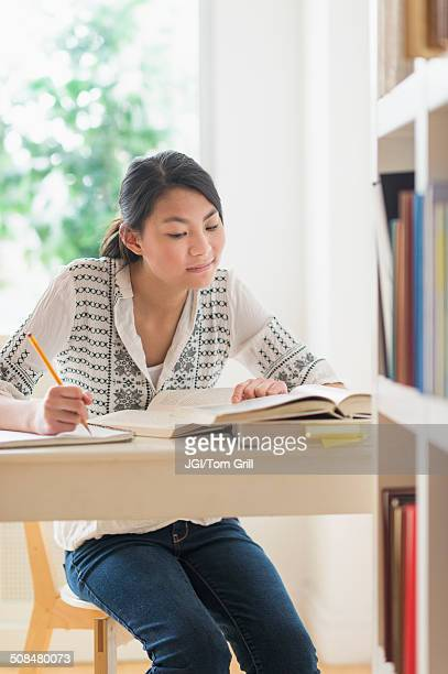 Mixed race teenage girl studying in library