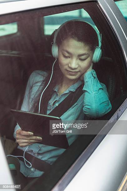 Mixed race teenage girl using digital tablet in backseat of car