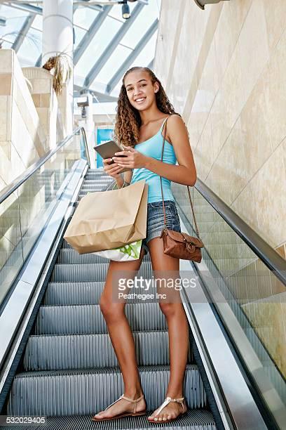 Mixed race teenage girl using digital tablet on escalator at shopping mall