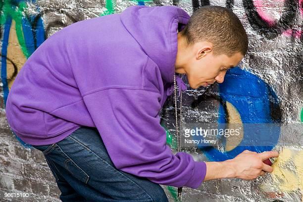Mixed race Teenager doing graffiti