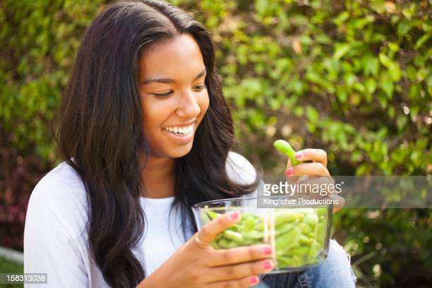 mixed race teenager eating edamame - edamame stock pictures, royalty-free photos & images