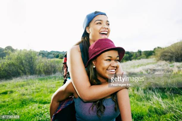mixed race teenager giving sister piggyback ride in field - ados lesbiennes en couple photos et images de collection