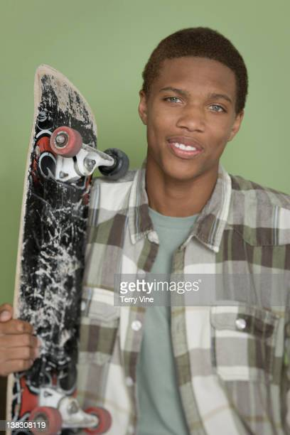 mixed race teenager holding skateboard - grey eyes stock pictures, royalty-free photos & images