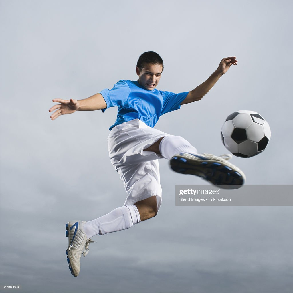 Mixed race teenager in mid-air kicking soccer ball : Stock Photo