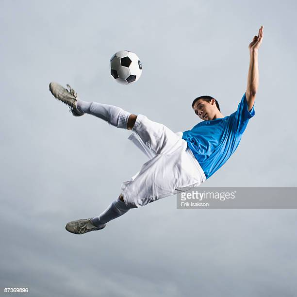 mixed race teenager in mid-air kicking soccer ball - teenagers only stock pictures, royalty-free photos & images