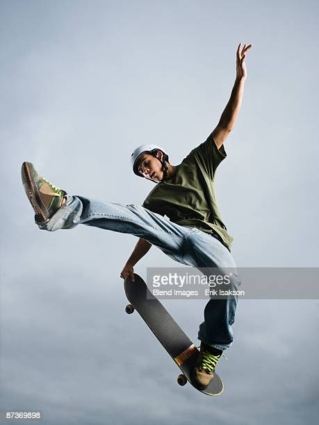 mixed race teenager in mid-air on skateboard - skating stock pictures, royalty-free photos & images