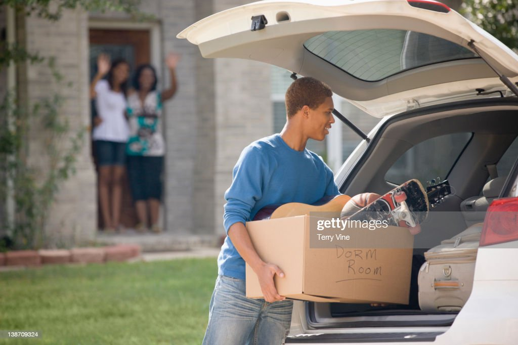 Mixed race teenager loading car for college : Stock Photo