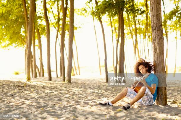 Mixed race teenager sitting in sand strumming guitar