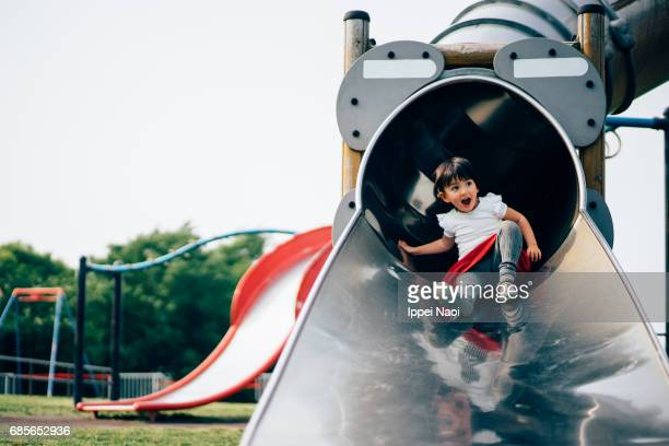 Mixed race toddler girl having fun at playground slide