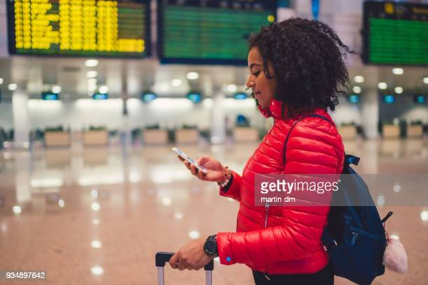 mixed race tourist woman checking for flight at airport - charles de gaulle airport stock photos and pictures