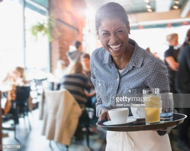 Mixed race waitress serving coffee and lemonade in cafe
