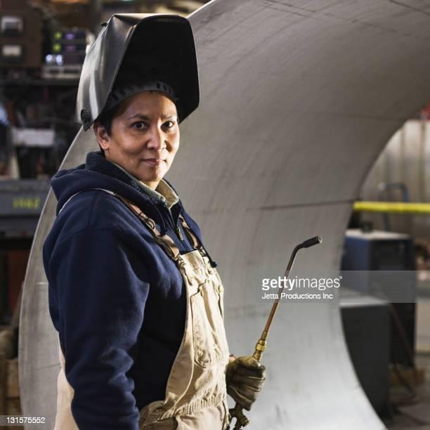 Mixed race welder in factory