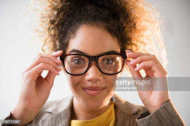 mixed race woman adjusting eyeglasses - adjusting stock pictures, royalty-free photos & images