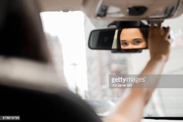 Mixed Race woman adjusting rear-view mirror in car