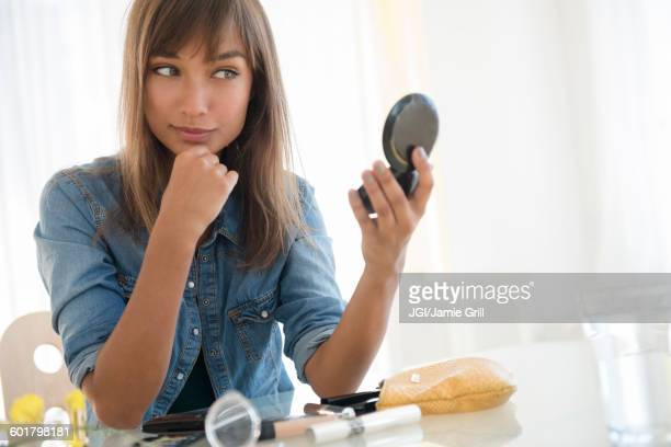 Mixed race woman admiring herself in mirror