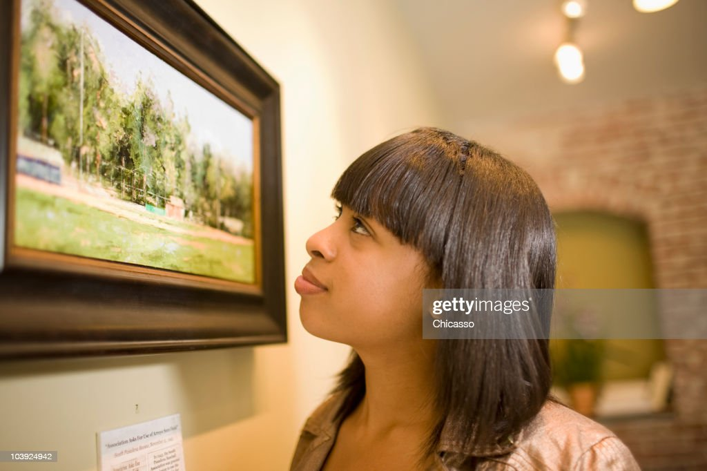 Mixed race woman admiring painting in gallery : Stock Photo
