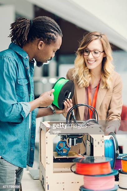 Mixed Race Woman and Man standing by 3D Printer.