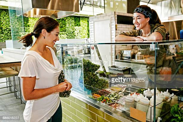 Mixed Race woman and worker in food court